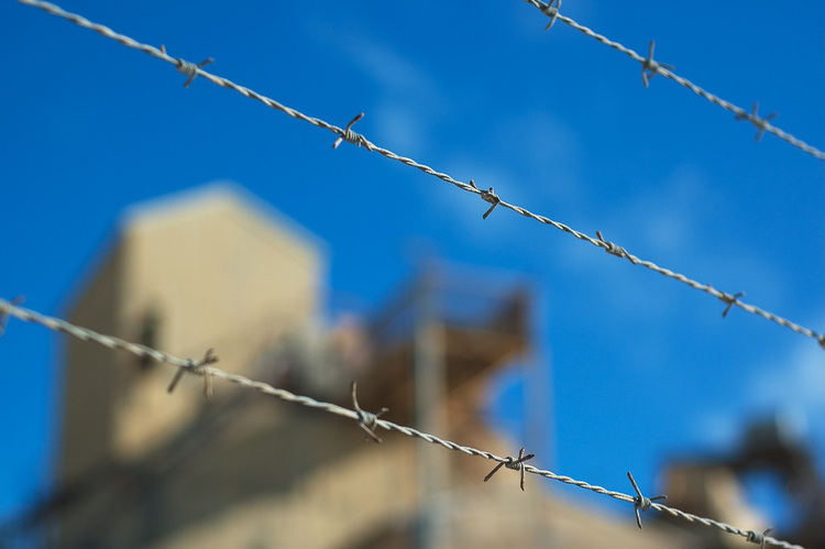 Barbed wire against a blue sky and buildings