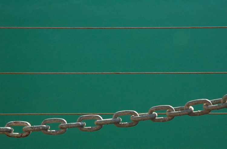 Fence chain links and wires, against an water background