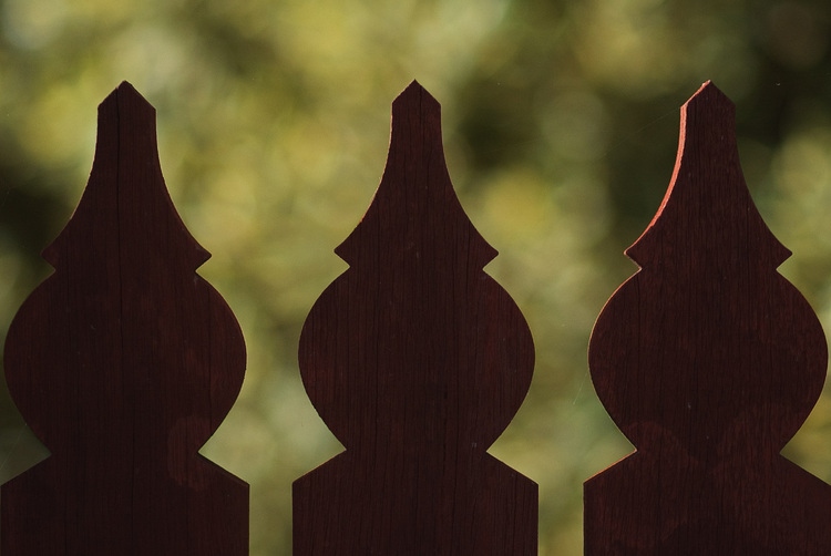 Three fence pickets silhouetted against foliage