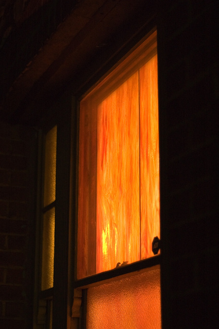 A glowing, orange-painted window at night