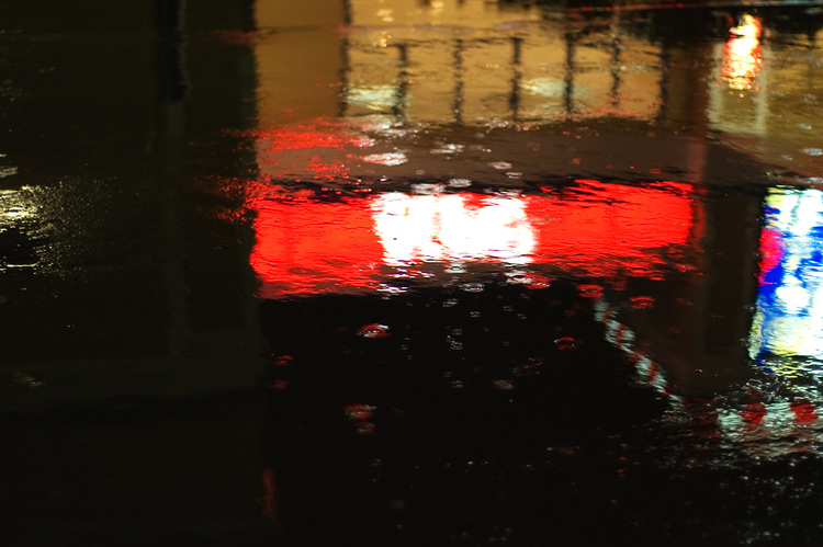 Bright signs, reflected in puddles