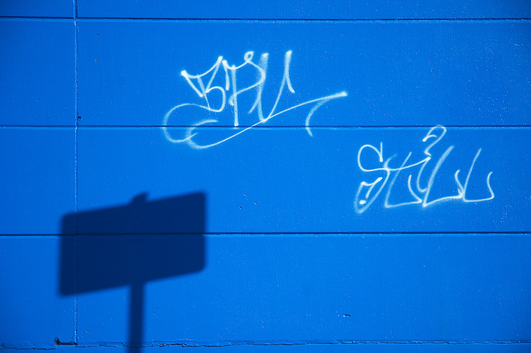 White graffiti on a blue wall, with the shadow of a sign on it