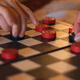 Hands moving pieces on a draughts board
