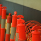 Orange safety cones, lined up next to a wall